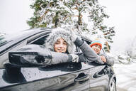 Portrait of smiling young couple leaning out of car windows in winter forest - OCMF00934