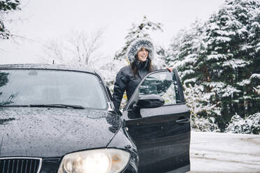 Smiling young woman standing beside parked car in winter forest looking at distance - OCMF00937