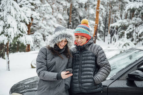 Smiling young couple leaning at parked car in winter forest looking at cell phone - OCMF00940