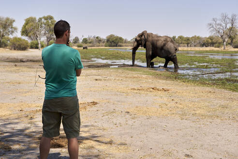 Man watching an elephant walking out of the water, Khwai, Botswana - VEGF00858
