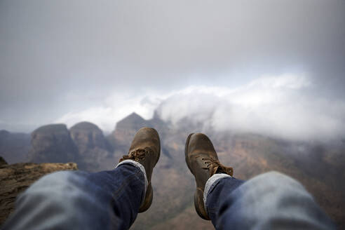 Man with a pair of vintage boots on the top of a hill overlooking the misty Blyde River Canyon, South Africa - VEGF00873
