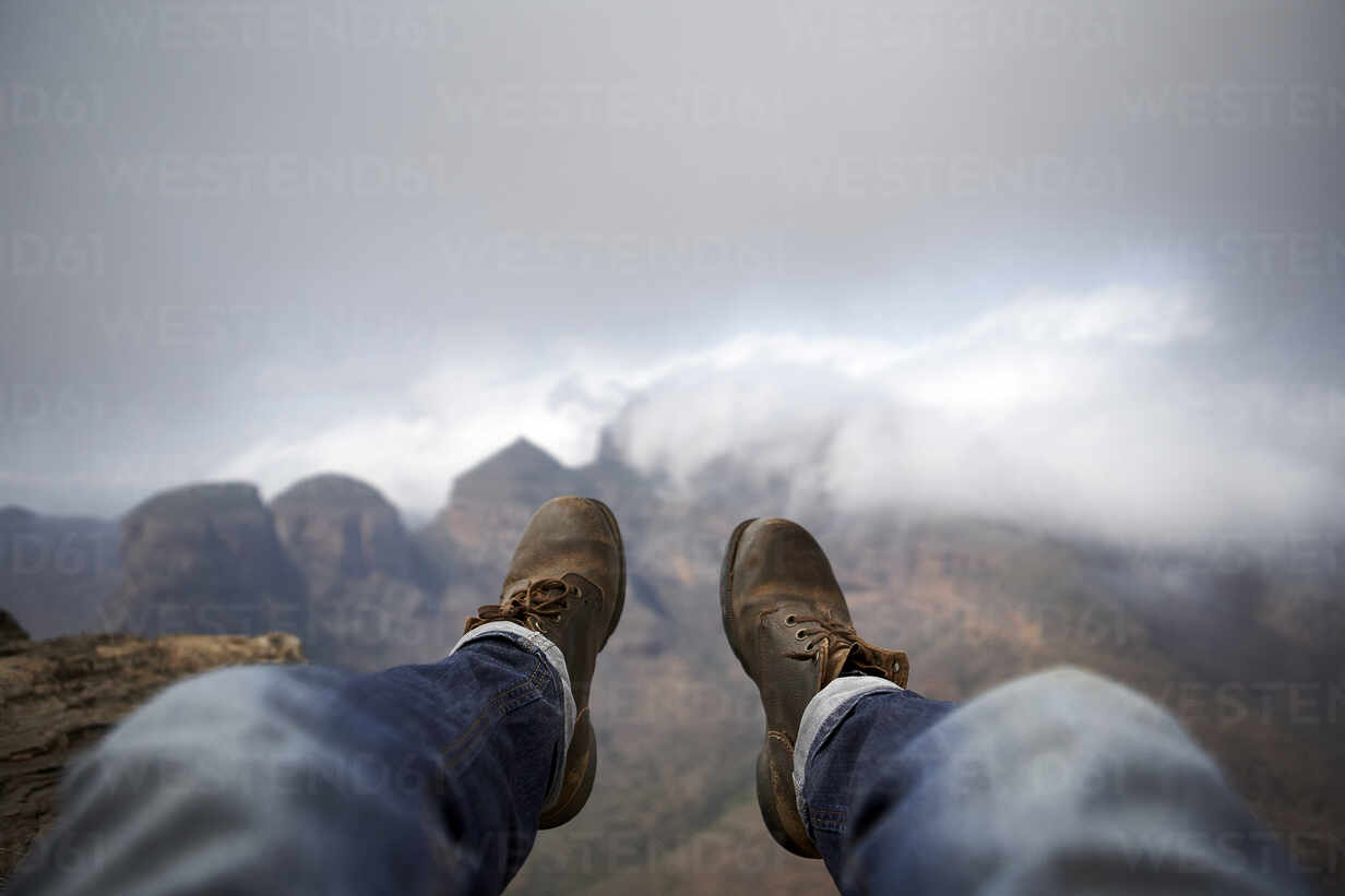 Man with a pair of vintage boots on the top of a hill overlooking the misty Blyde River Canyon, South Africa - VEGF00873 - Veam/Westend61