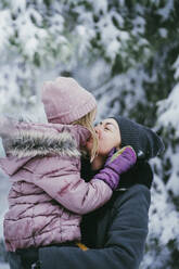 Mother kissing her little daughter in winter forest - PSIF00338