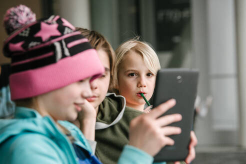 Girl and brothers looking at digital tablet in airport, head and shoulders - ISF23011