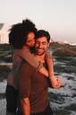 Couple enjoying view of sunset on beach - ISF23152