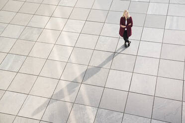 Blond businesswoman standing on floor, arms crossed and looking at camera, from above - AHSF01363