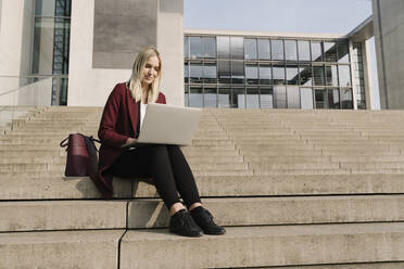 Blond businesswoman with laptop in the background of modern office building - AHSF01369