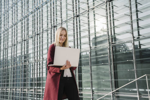 Blond businesswoman with laptop in the background of modern office building - AHSF01372