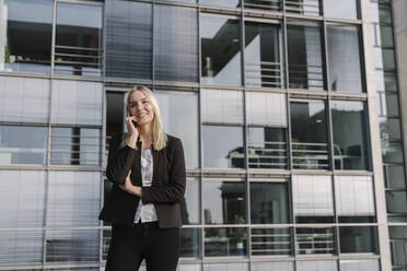 Blond businesswoman using smartphone in the background modern building - AHSF01378