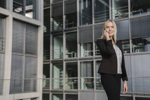 Blond businesswoman using smartphone in the background modern building - AHSF01381