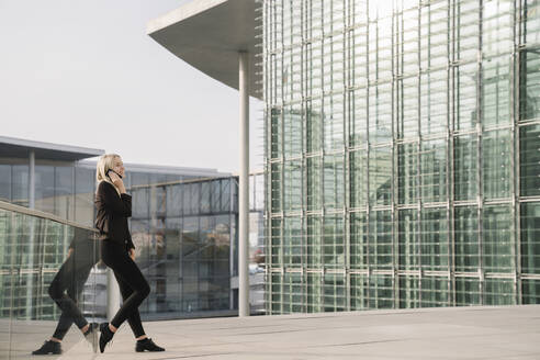 Blond businesswoman using smartphone in the background modern buildings - AHSF01384