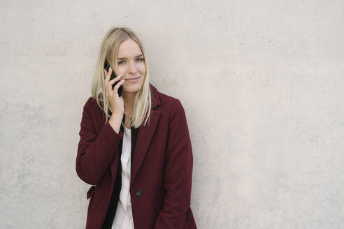 Blond businesswoman using smartphone, leaning on a wall, looking at camera - AHSF01396