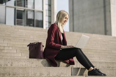Blond businesswoman using laptop, sitting on step - AHSF01399