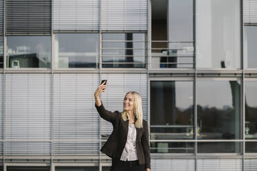 Blond businesswoman using smartphone and taking a selfie - AHSF01405