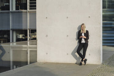 Blond businesswoman using smartphone leaning on wall - AHSF01408