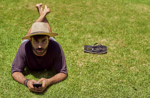 Man lying in grass using his smartphone - VEGF00889