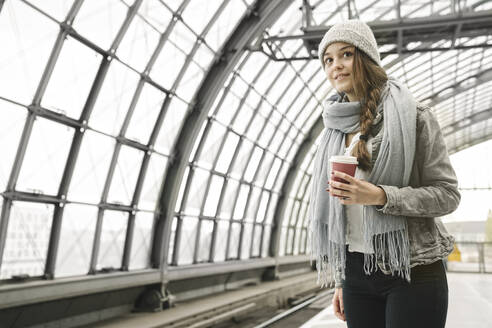 Young woman with takeaway coffee waiting at the station platform, Berlin, Germany - AHSF01424