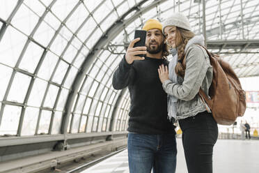 Happy young couple using smartphone at the station platform, Berlin, Germany - AHSF01436