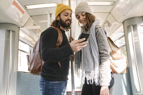 Young couple using smartphone on a subway - AHSF01457