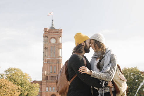 Young couple embracing with Rotes Rathaus in background, Berlin, Germany - AHSF01463