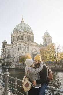 Young couple embracing with Berlin Cathedral in background, Berlin, Germany - AHSF01469