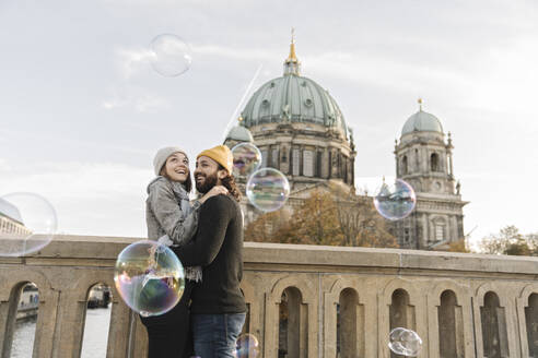 Happy young couple embracing watching soap bubbles in the city, Berlin, Germany - AHSF01475