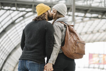 Young couple kissing at the station platform, Berlin, Germany - AHSF01490