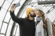 Young couple taking a selfie at the station platform, Berlin, Germany - AHSF01493