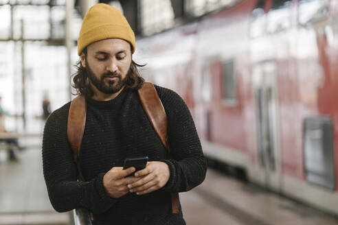 Young man using smartphone at the station platform, Berlin, Germany - AHSF01502