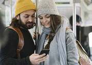 Young couple using smartphone on a subway - AHSF01505