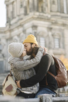 Affectionate young couple kissing with Berlin Cathedral in background, Berlin, Germany - AHSF01514