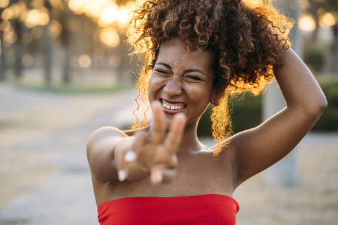 Young happy woman expressing V gesture with fingers - MPPF00311