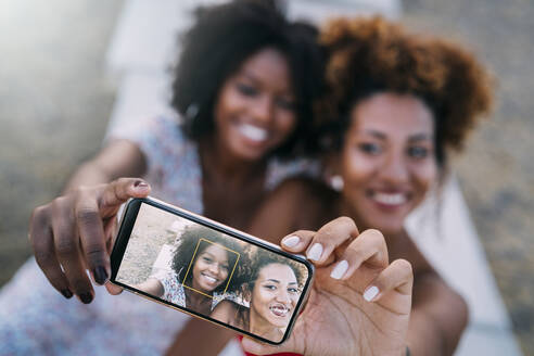 Young women smiling and making a selfie with their smart phone in a park - MPPF00317