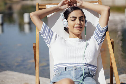 Young woman wearing headphones relaxing in a deckchair - JSMF01386