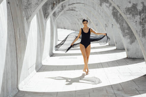 Young woman wearing black swimsuit dancing in an archway - JSMF01398