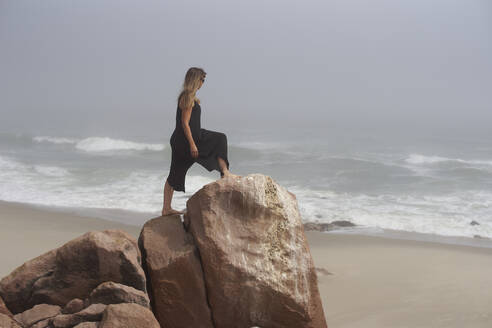 Woman standing on a rock looking to the ocean, Cape Cross, Namibia - VEGF00950