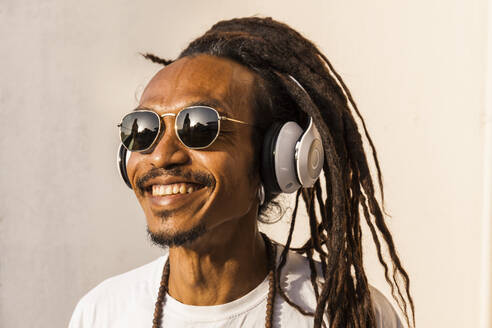 Portrait of smiling mature man with dreadlocks and headphones, listening music and looking sideways - TCF06210