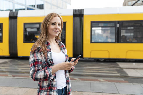 Portrait of a smiling woman in the city with a tram in the background, Berlin, Germany - WPEF02295