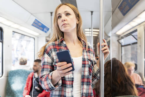 Woman with smartphone on the subway, Berlin, Germany - WPEF02307