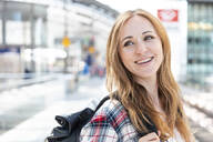 Happy woman on the station platform, Berlin, Germany - WPEF02313
