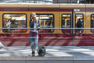 Smiling woman on the phone at the station, Berlin, Germany - WPEF02319
