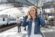Smiling woman listening to music with headphones at the station, Berlin, Germany - WPEF02322