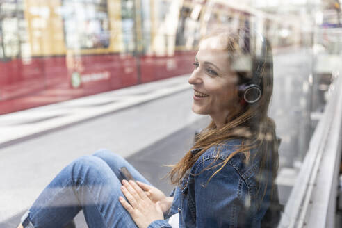 Happy woman with smartphone and headphones waiting at the station, Berlin, Germany - WPEF02331