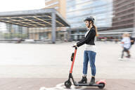Woman riding e-scooter in the city, Berlin, Germany, Berlin, Germany - WPEF02340