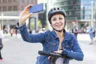 Smiling woman with e-scooter taking a selfie in the city, Berlin, Germany - WPEF02352