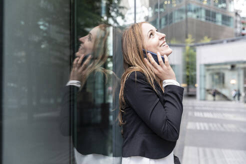 Smiling businesswoman on the phone in the city - WPEF02364