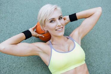 Blonde woman lying on basketball - MADF01408