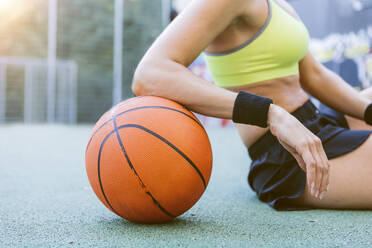 Young woman sitting and resting on basketball - MADF01411