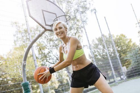 Blonde woman playing basketball - MADF01414