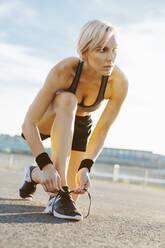 Blonde woman jogging, tying shoes - MADF01420